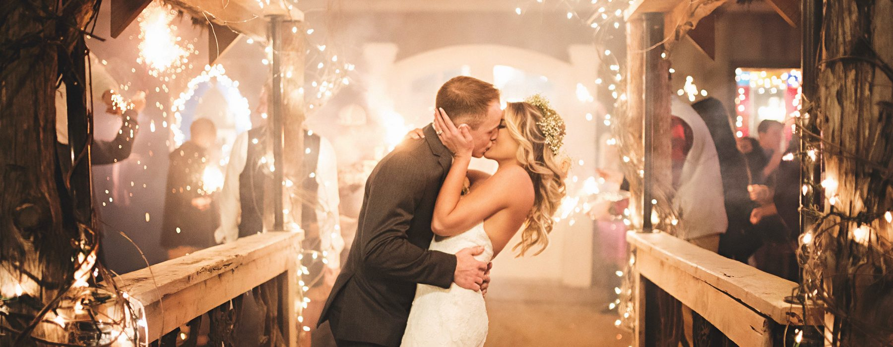 Bride and groom kiss under twinkle lights
