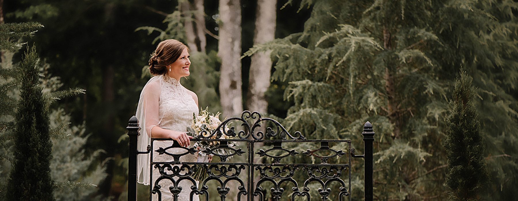 A bride stands next to an iron gate