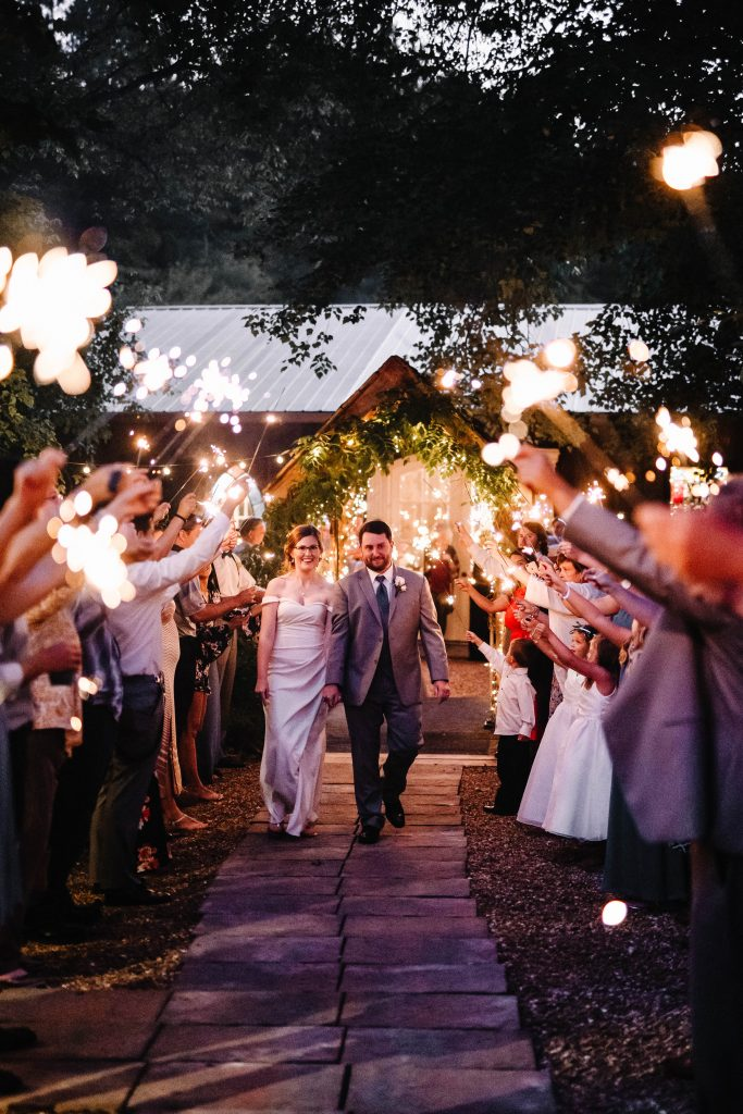 A couple exits their wedding through sparklers
