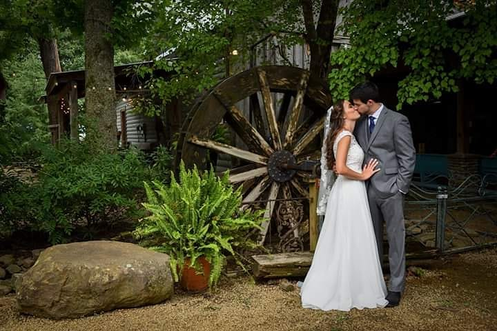 Bride and groom kiss by a water wheel