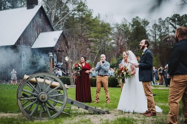 A couple in wedding attire fires a cannon